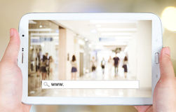 Hand holding tablet with www. on search bar over blur store back Royalty Free Stock Photos