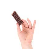 Hand holding tasty dark chocolate bar. Royalty Free Stock Photos