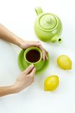 Hand holding tea cup with kettle lemon high angle Royalty Free Stock Photography