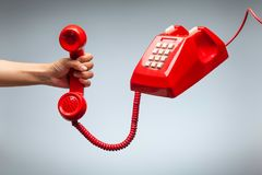 Hand holding telephone, classic red telephone receiver. Old telephone  on white background flying in weightlessness Stock Photography