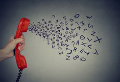 Hand holding telephone handset with alphabet letters coming out. Too many words Stock Image