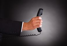 Hand Holding Telephone Receiver Over Black Background Stock Images