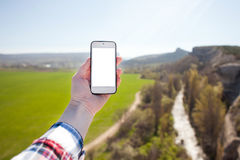 Hand holding telephone on spring landscape background. technology and trevelling concept. Royalty Free Stock Image