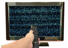Hand holding television remote control pointing to glitch on screen background stock photography