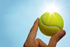 Hand holding tennis ball up to the sky. A man's hand holding a tennis ball up to a blue sky with the sun behind it Royalty Free Stock Photos