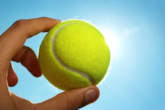 Hand holding tennis ball up to the sky. A man's hand holding a tennis ball up to a blue sky with the sun behind it Royalty Free Stock Photography