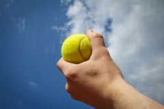 Hand holding tennis ball up to the sky Royalty Free Stock Images