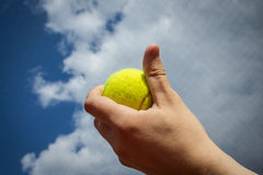 Hand holding tennis ball up to the sky Stock Photo