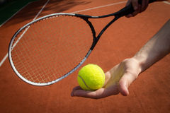 Hand holding tennis racket and ball on court. Landscape image of a player's hand holding tennis racket and ball on court Royalty Free Stock Photo