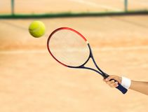 Hitting a tennis ball. Hand holding a tennis racket hitting a ball on a clay court Royalty Free Stock Images