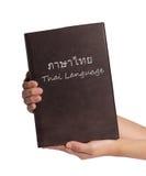 Hand holding Thai language book isolated on white background Royalty Free Stock Image