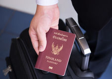 Hand holding Thai passport, ready to travel Stock Photo