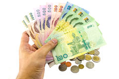 Hand holding thailand banknotes and coins isolated Stock Photography