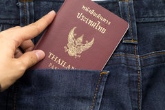 Hand holding thailand passport insert back pocket blue jean pant. Hand of woman holding thailand passport insert back pocket blue jean pants, this image for stock photos