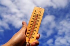 Hand Holding Thermometer. With extreme temperature with nice blue sky background Stock Photos