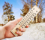 Hand holding a thermometer. Man's hand holding a thermometer with low against the cold of the winter forest Stock Photography