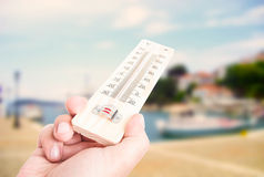 Hand holding thermometer on city with lake background. As summer heat concept Stock Photography