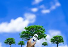 Thermometer against green trees and blue skies royalty free stock photos