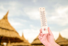 Hand holding thermometer on straw umbrellas background Stock Images