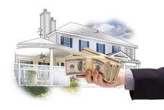 Hand Holding Thousands In Cash Over House Drawing and Photo Royalty Free Stock Images
