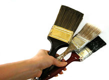 Hand Holding Three Paint Brushes. Close up of a painter holding three brushes royalty free stock images