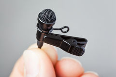 Hand holding Tie-Clip Microphone. Close-up of a hand holding a tie-clip microphone with a plain background Stock Photos