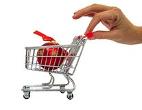 Hand holding a tiny shopping cart with a red decoration Christmas ball. Isolated on white background Stock Photography