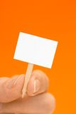 Hand Holding Tiny Sign on Orange with Copy Space Stock Photography