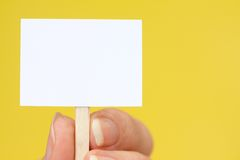 Hand Holding Tiny Sign on Yellow with Copy Space Stock Photos