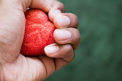 Hand holding on to heart stock images
