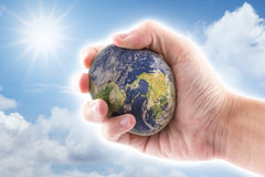 Hand is holding to the stone world on blue sky. Background, the world map by nasa Stock Images