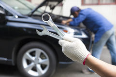 Hand holding tools and car service Stock Photos
