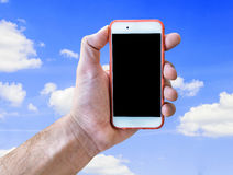 Hand holding touch screen mobile phone isolated on cloudy blue sky Stock Photography