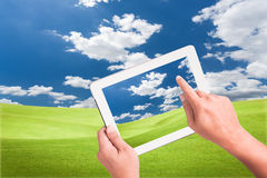 Hand holding a touchpad pc. With green field stock image