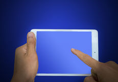 Hand holding a touchpad pc, one finger touches the screen on blu. E background technology Stock Photo