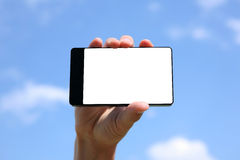 Hand holding touchscreen smart phone. On blue sky background Stock Images