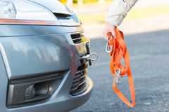 Hand holding tow rope. Near towing hook assembled to a broken car Stock Photo