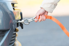 Hand holding tow rope. Near towing hook assembled to a broken car Stock Photography