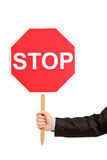 A hand holding a traffic sign stop. Isolated against white background Royalty Free Stock Photo