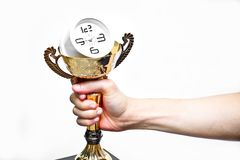 Hand holding trophy with a clock. A trophy with a clock in side representing time management royalty free stock photo