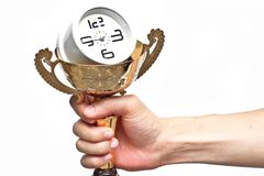 Hand holding trophy with a clock. A trophy with a clock in side representing time management stock photo