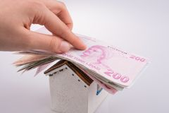 Hand holding Turkish Lira banknotes on the roof of a model house. On white background royalty free stock image