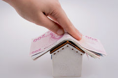 Hand holding Turkish Lira banknotes on the roof of a model house Stock Photos