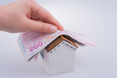 Hand holding Turkish Lira banknotes on the roof of a model house Royalty Free Stock Images