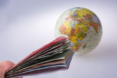 Hand holding Turkish Lira banknotes by the side of a model globe Stock Images