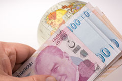 Hand holding Turkish Lira banknotes by the side of a model globe Stock Photo
