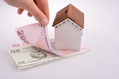 Hand holding Turkish Lira banknotes by the side of a model house Royalty Free Stock Images