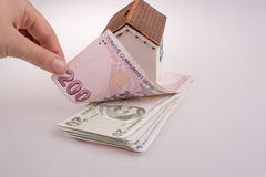 Hand holding Turkish Lira banknotes by the side of a model house Royalty Free Stock Photography