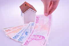 Hand holding Turkish Lira banknotes by the side of a model house Stock Photography