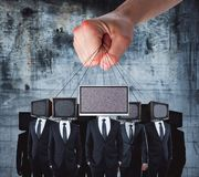 Manipulation and brainwash concept. Hand holding TV headed businessmen on rope. Manipulation and brainwash concept Royalty Free Stock Photo